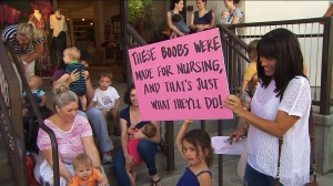 A girl holds up a sign in support of breast feeding outside the Beverly Hills Anthropologie store on Wednesday, Aug. 20, 2014. (Credit: KTLA)