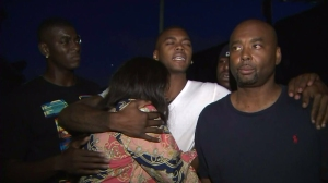 Tritobia Ford is comforted by family members on Aug. 12, 2014, the night after her son was fatally shot by police. (Credit: KTLA)