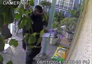 Jerry Coleman is accused of being the robber shown in this surveillance video image posing as a flower deliveryman on Aug. 11, 2014.