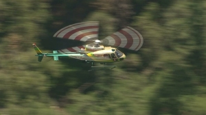 A Los Angeles County Sheriff's Department helicopter flies over a search area for possible missing people on Mount Baldy on Aug. 4, 2014. (Credit: KTLA)