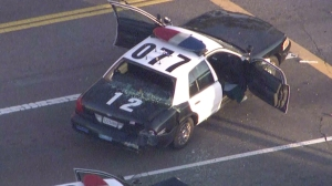 A pursuit ended at the intersection of 37th and Hill streets in South Los Angeles before one of two gunman was shot and killed by police on Monday, Aug. 18, 2014, authorities said. A second shooter was taken into custody. (Credit: KTLA)