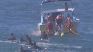 A lifeguard boat rescued a distressed swimmer and three lifeguards who were struggling at the Wedge in Newport Beach on Aug. 27, 2014. (Credit: KTLA)