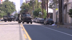 A SWAT armored truck helped save officers in a shootout on Aug. 18, 2014, police said. An alleged gunman's body lay in the street after the shooting. (Credit: KTLA)