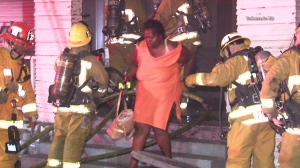A woman exited a home in the South Park neighborhood of Los Angeles after a fire broke out on Monday, Aug. 11, 2014. (Credit: On Scene Video)