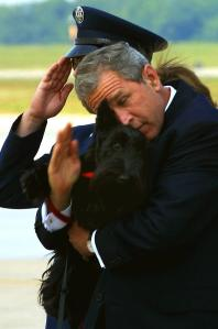 President George W. Bush tries to salute the security officers at the steps of Air Force One as he holds his dog Barney, after returning from a speech to the U.S. Conference of Mayors in Detroit. (Credit: Paul J. Richards/AFP/Getty Images)