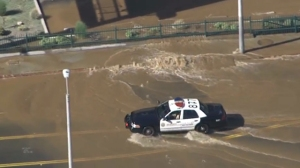 A Los Angeles Police Department car car be seen driving through a flooded street in West Hollywood after a water main break on Sept. 26, 2014. (Credit: KTLA)