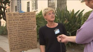 Annie Preece of Beverly Grove stands next to a sign on Tuesday, Sept. 9, 2014, warning dog owners to pick up after their pets. (Credit: KTLA)