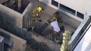 Firefighters appeared to be helping a fellow first responder after the flames were out at a West Hollywood condo fire on Sept. 18, 2014. (Credit: KTLA)