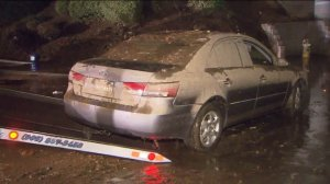 A mud-caked car was towed after being trapped in floodwater on Sept. 8, 2014. (Credit: KTLA)
