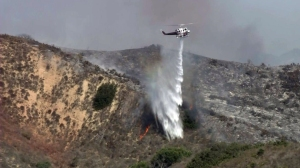 A helicopter drops water on the Foothill Fire in Ventura on Sept. 29, 2014. (Credit: KTLA)