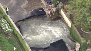 Water is seen swirling from beneath a collapsed road in Encino on Monday, Sept. 8, 2014. (Credit: KTLA)