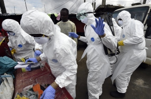 Members of the Red Cross put on their protective suits as they get ready to collect the body of a person suspected of dying from the Ebola virus in the West Point district of the Liberian capital Monrovia, on October 4, 2014. By far the most deadly epidemic of Ebola on record has spread into five west African countries since the start of the year, infecting more than 7,000 people and killing about half of them.(Credit: Pascal Guyot/AFP/Getty Images)