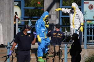 First responders wear full biohazard suits while responding to the report of a woman with Ebola-like symptoms at the Dallas Area Rapid Transit White Rock Station Oct. 18, 2014, in Dallas. The woman reportedly lives in the same apartment complex as Thomas Eric Duncan, the Liberian who was the first patient diagnosed with Ebola in the United States, and who died on October 8. (Credit: Chip Somodevilla/Getty Images)