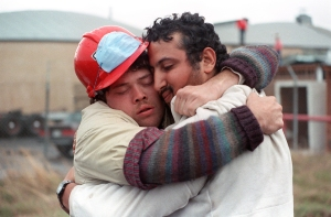 Two search and rescue workers embrace after rescuing a man from a collapsed freeway structure in Oakland on Oct. 21, 1989. (Credit: CHRIS WILKINS/AFP/Getty Images)