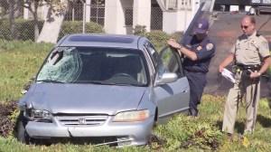 Investigators examine a car that struck Ventura County Deputy Eugene Kostiuchenko on Oct. 28, 2014. (Credit: KTLA)