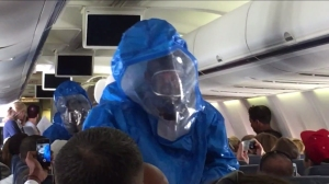 A man who screamed that he had Ebola on a crowded plane was escorted of the aircraft by a teams of men in haz-mat suits. (Credit: Patrick Narvaez/Jukin Media, Inc.)