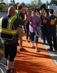 Newly hire Amazon employees walk down the orange carpet for their first day of work at the Redlands fulfillment center in this photo provided by Amazon in October 2014.