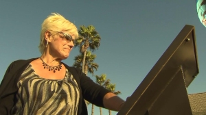 The mother of Robin Samsoe, a 12-year-old girl who was abducted and killed in 1979, admires a memorial created in honor of her daughter. It was scheduled to be unveiled in Huntington Beach on Oct. 19, 2014. (Credit: KTLA)