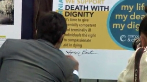 Supporters sign an oversized petition in favor of  death with dignity laws in California.  (Credit: KTLA)
