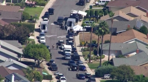 "SWAT and patrol cars were outside the Avenida Calidad address given out by Jason ""Mayhem"" Miller, who was live-tweeting the response, on Oct. 9, 2014. (Credit: KTLA)"