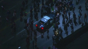 Protesters briefly surrounded a CHP patrol car on Jefferson Boulevard on Nov. 25, 2014. (Credit: KTLA)