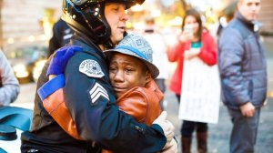 "In a photo shared over 150,000 times on Facebook, 12-year-old Devonte Hart, who was previously holding a sign stating ""Free Hugs,"" is seen embracing Portland, Oregon, police Sgt. Bret Barnum on Nov. 25, 2014. (Credit: Johnny Nguyen/ http://www.chambersvisuals.com )"