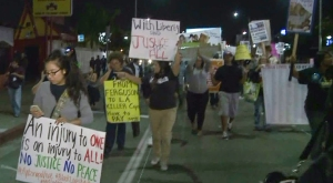 Dozens of people march down Martin Luther King Jr. Boulevard Monday protesting the grand jury decision in the Michael Brown shooting case. (Credit: KTLA)