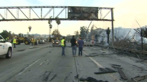 Fire crossed over onto the 110 Freeway in downtown L.A. Dec. 8, 2014, damaging multiple large metal traffic signs. (Credit: KTLA)