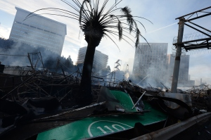 A freeway sign is mangled in the aftermath of a huge fire in downtown Los Angeles on Dec. 8, 2014. Flames spread for a whole city block, nearly a million square feet, officials said. (Credit: ROBYN BECK/AFP/Getty Images)