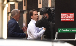 Two hostages run for cover behind a policeman during a hostage siege in the central business district of Sydney on Monday, Dec. 15, 2014. Five people ran out of a Sydney cafe where a gunman has taken hostages and displayed an Islamic flag against the window, police said. (Credit: William West/AFP/Getty Images)