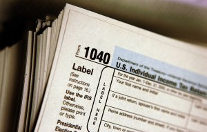The top of a form 1040 individual income tax return is seen atop a stack on the same in this file photo. (Credit: Tim Boyle/Getty Images)
