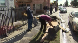 "People were cleaning up after residents described a ""tornado"" ripping the roof off a house in South L.A. on Dec. 12, 2014. (Credit: KTLA)"