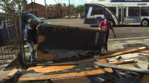 Residents were cleaning up after a small tornado struck South L.A. Dec. 12, 2014. (Credit: KTLA)