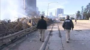 Investigators walk alongside the smoldering ruins of a building that burned in downtown L.A. on Dec. 8, 2014. (Credit: KTLA)