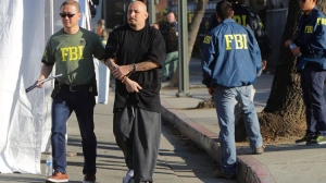 A suspect is processed in downtown Los Angeles on Wednesday morning as authorities moved to arrest dozens of Los Angeles gang members indicted under the federal Racketeer Influenced and Corrupt Organization statutes. (Irfan Khan/Los Angeles Times)