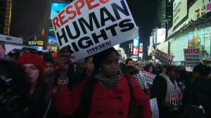 A woman is pictured protesting in Times Square Wednesday, Dec. 3, 2014, over the Grand Jury decision on Eric Garner. (Credit: CNN)