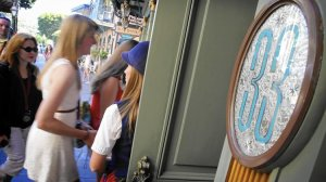 Victoria Dale, guest relations guide, holds open the door to the Club 33 restaurant for visitors on a special paid VIP tour at Disneyland in 2013. (Credit: Don Bartletti/Los Angeles Times)