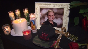 A memorial was set up outside the home where 12-year-old Roman Martinez was fatally struck by a car while riding his new scooter on Dec. 26, 2014. (Credit: KTLA)