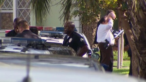 Police surround a home in Mid-City near a triple shooting that left three people in critical condition on Wednesday, Dec. 17, 2014. (Credit: KTLA)