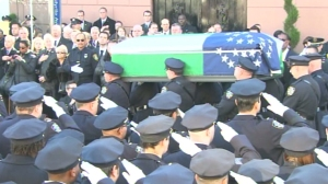 A moment of silence was held as a casket carrying NYPD Officer Rafael Ramos was carried from his funeral, held Dec. 27, 2014. (Credit: CNN)