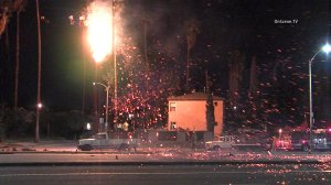 A palm tree caught fire in Mid-City on Dec. 25, 2014. (Credit: OnScene.TV)
