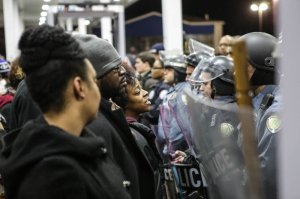 Police and demonstrators stand face-to-face following the Dec. 23, 2014, police shooting death of Antonio Martin, 18, at a Berkeley, Missouri gas station. Police said Martin pointed the gun at an officer and the officer fired shots, fatally wounding the teen. (Credit: L. Bryant/St. Louis American)