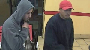 Two alleged armed robbers are seen in a surveillance image released by the Santa Ana Police Department on Tuesday, Dec. 23, 2014.