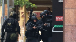 Armed police are seen outside the Lindt Cafe, Martin Place on Dec. 15, 2014, in Sydney, Australia. (Credit: Mark Metcalfe/Getty Images)