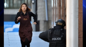 One of the hostages runs toward police from a cafe in the central business district of Sydney on Monday, Dec. 15, 2014. Five people ran out of a Sydney cafe where a gunman has taken hostages and displayed an Islamic flag against the window, witnesses and police said.(Credit: Saeed Khan/AFP/Getty Images)