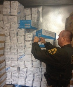 A Los Angeles County sheriff's investigator photographs cases of stolen meat that were found at a cold-storage facility in downtown Los Angeles. (Credit: L.A. County Sheriff's Department)