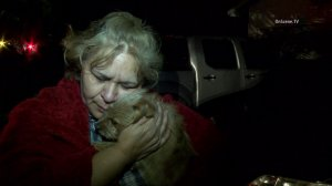 Vera Mendez cradles her dog Foxy, who was credited with saving Mendez's family from a fire in Santa Ana on Jan. 21, 2015. (Credit: OnScene TV)