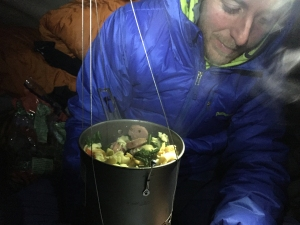 Tommy Caldwell eating dinner on the side on the Dawn Wall on Dec. 29, 2014.  (Credit: Kevin Jorgeson via Adidas Outdoor)