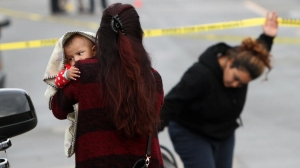 A family member holds an infant who was in a vehicle pursued by police on Jan. 10, 2015. (Credit: Bob Chamberlin / Los Angeles Times)