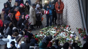 Mourners gather around a makeshift memorial during a vigil, one of several held around the world, to honor the 10 journalists and two police officers murdered when gunmen opened fire at the Parisian offices of the French satirical publication Charlie Hebdo on Jan. 7, 2015. (Credit: Adam Berry/Getty Images)